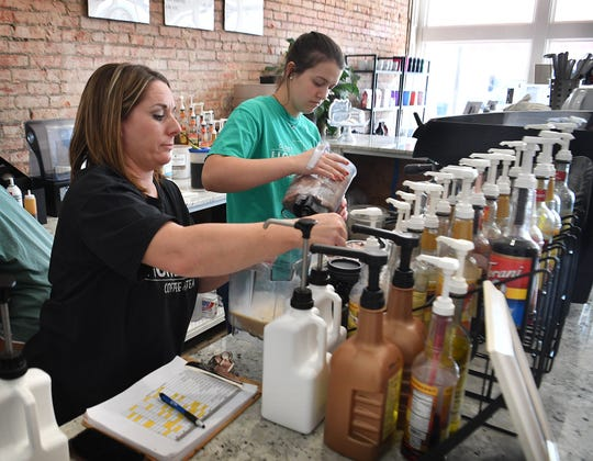 Holly Bailey, left, owner of Hometown Coffee & Tea in Olney, Texas, helps her employee, Jae Montgomery, fill a large order to go. Her business has done well despite the economic downturn of the pandemic.
