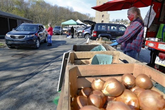 Workers from Sarver farms, right, wear protective masks, beside the onions, potatoes and vegetables they are selling to patrons driving by in their cars at the Greensburg Farmers' Market opening day, Saturday, April 25, 2020, in Greensburg, Pa.
