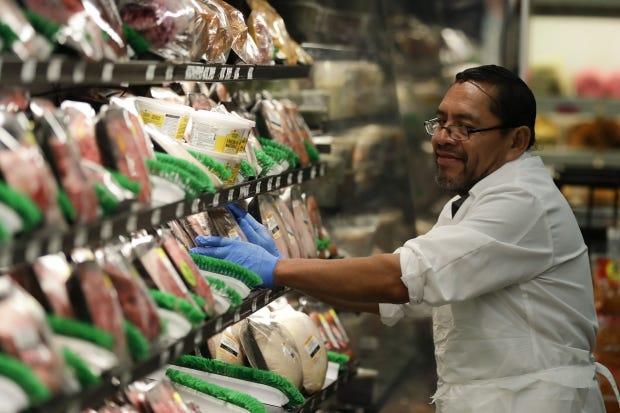 Jose Perez stocks meat wearing rubber gloves at Northgate Gonzãlez Market on Tuesday, March 17, 2020, in Santa Ana, Calif. In light of the coronavirus concerns the Northgate market chain opened the store one hour early for seniors 65-years and older and disabled.