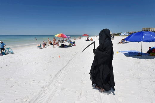 "Dressed as the Grim Reaper, Florida Attorney Daniel Uhlfelder talks with reporters after walking the newly opened beach near Destin, Fla on Friday, May 1, 2020. Uhlfelder was protesting the Walton County (Florida) Commission's decision to reopen the county's beaches in spite of the COVID-19 pandemic.  ""In these circumstances, I can see no rational reason to open our beaches, effectively inviting tens of thousands of tourists back into our community"" Uhlfelder said in a news release. ""If by dressing up as the 'Grim Reaper' and walking our beaches I can make people think and potentially help save a life – that is the right thing to do."""