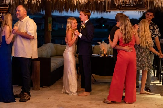 April 18, 2020: Royal Palm Beach, FL, USA  Paige Houck and Dominick Grosso, center, dance with their families during prom night at the Gosso's home. Their school prom was canceled because of the coronavirus.