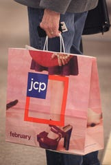 A shopper carries a bag at a J.C. Penney store in the North Riverside Park Mall in North Riverside, Illinois  on Feb. 1, 2012.