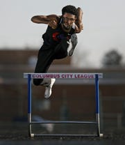 Eastmoor Academy track star Ira Graham IV jumps over a hurdle at Eastmoor Academy High School Stadium in Columbus, Ohio on April 8, 2020.  Graham lost his spring track season due to the coronavirus.