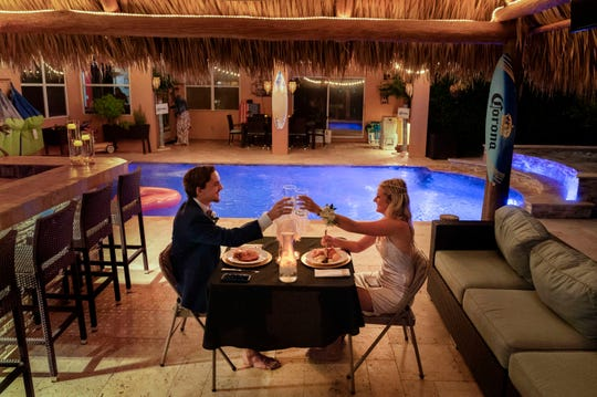 April 18, 2020: Royal Palm Beach, FL, USA Mandatory  Royal Palm Beach High School seniors Dominick Grosso and Paige Houck toast each other as they spend their prom night together in the backyard of the Grosso home. Their school prom was canceled because of the coronavirus.