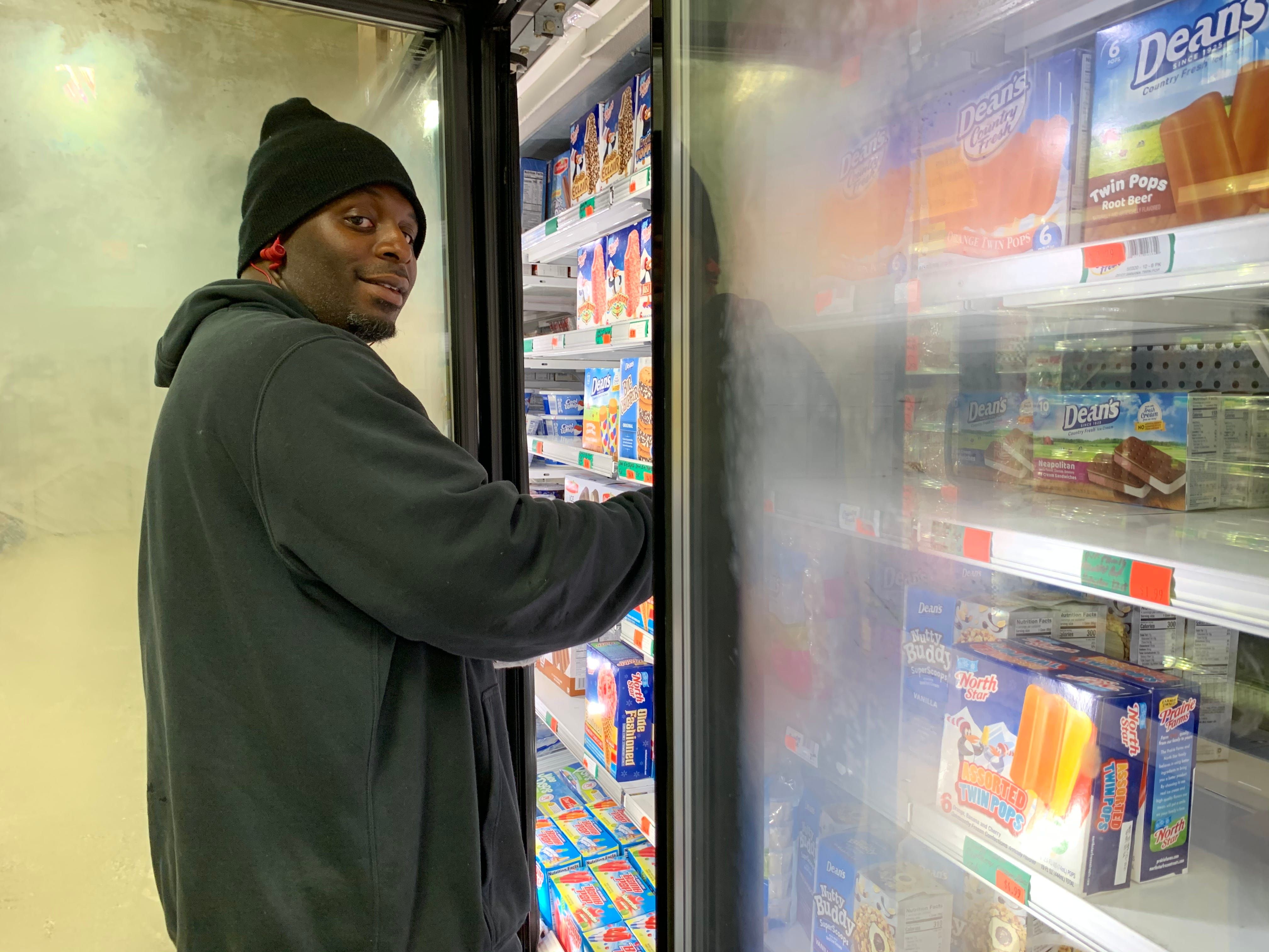 Ira Carroll restocks the ice cream in the frozen section of Saturn Super Foods, in Detroit's 48228 ZIP code, where he has worked for 22 years.