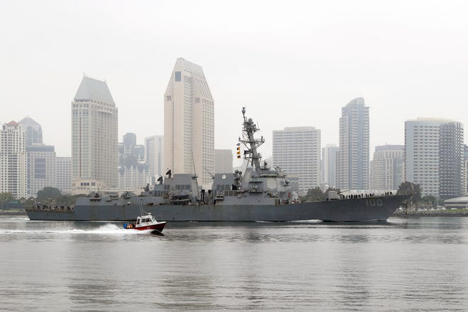 In this April 28, 2020, photo, the USS Kidd passes downtown San Diego as it returns to Naval Base San Diego, seen from Coronado, Calif. Lessons learned from a coronavirus outbreak aboard the aircraft carrier USS Theodore Roosevelt played a central role in limiting damage when the virus hit the USS Kidd at sea.