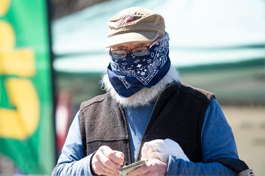 A customer prepares to pay for vegetables at the Fusda Farm stand at the Capital City Farmers Market in Montpelier on Saturday, May 2, 2020.