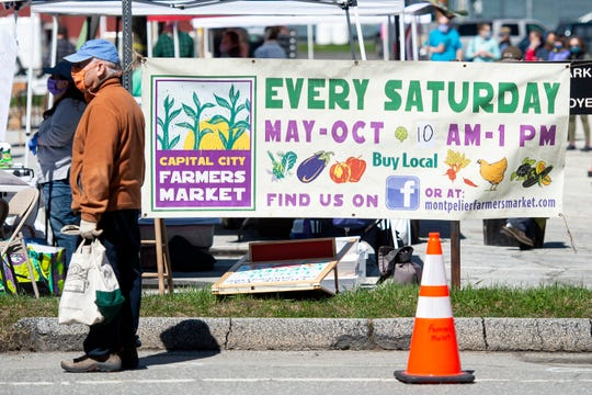A masked customer waits with his gloves and bag before entering the Capital City Farmers Market in Montpelier on Saturday, May 2, 2020.