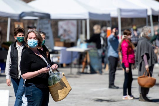 A Capital City Farmers Market customer waits in line to pick up an item in Montpelier on Saturday, May 2, 2020.