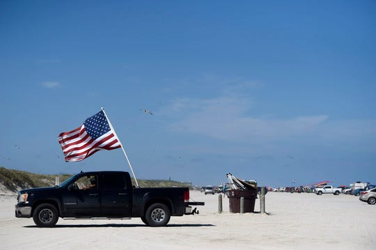 A truck holds an American flag, Saturday, May 2, 2020, in Port Aransas. Gov. Greg Abbott first phase to reopen Texas began Friday, May 1.