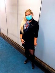 Flight attendant Taylor Hohensee of Des Moines is wearing a mask while assisting passengers during flights.