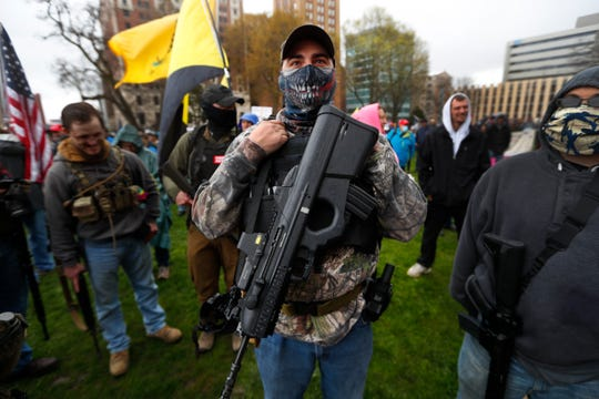 A protester carries his rifle at the State Capitol in Lansing, Mich., Thursday, April 30, 2020. Hoisting American flags and handmade signs, protesters returned to the state Capitol to denounce Gov. Gretchen Whitmer's stay-home order and business restrictions due to the coronavirus pandemic while lawmakers met to consider extending her emergency declaration hours before it expires.