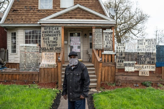 """Detroiter Mike Forbes stands in front of his house on Detroit's east side on Thursday, April 30, 2020 where he has expressed his fears and frustrations to his neighbors about the coronavirus with signs on his house. """"They have to realize this is for real,"""" he said. """"A lot of us don't realize this is for real. It's not like they're just saying that. That's why I put it up there, for all to know."""""""