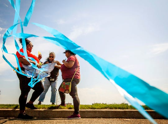Terri Gavin, left, Kimberly Johnson, middle and Angel Johnson, all of Detroit, work together to untangle two kites they were preparing to fly at Belle Isle Park in Detroit on May 2, 2020. Warm temperatures and bright sunshine brought people outside in large numbers.