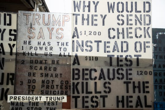 Handmade signs are seen around Detroiter Mike Forbes house on Detroit's east side on Thursday, April 30, 2020, where he has expressed his fears and frustrations to his neighbors about the coronavirus.