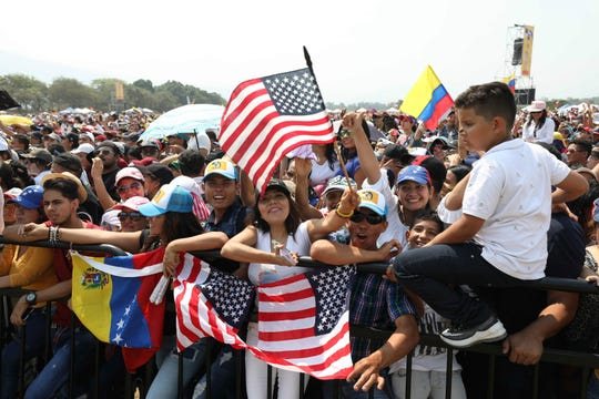 FILE - In this Feb. 22, 2019 file photo, people wave Venezuelan and U.S. flags during the Venezuela Aid Live concert on the Colombian side of the Tienditas International Bridge near Cucuta, Colombia, on the border with Venezuela.
