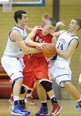 Bosse's Bo Burkhart (22) is pressured by Castle's Blake Simmons (50) and Kyle Aiton (14) during the second half of an Old National Bank Southern Indiana Athletic Conference semifinal at Castle.