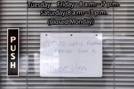 "A handwritten sign that says ""closed until further notice due to the Chinese Virus"" hangs in the door of a beauty salon on Main Street in Sebree, Ky., Thursday, April 30, 2020. The town of Sebree is a located a few miles south of a Tyson Foods poultry plant, which has had more than 70 workers test positive for COVID-19."