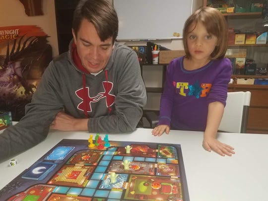 """Ross Miller and his daughter, Luna, play """"Ghost Fightin' Treasure Hunters."""" The Miller house is stocked with board games, geared toward both children and adults."""