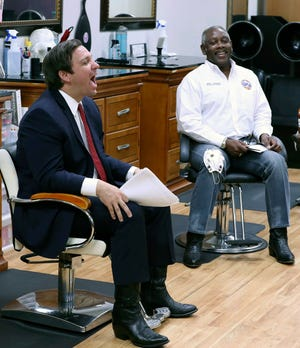 "Florida Gov. Ron DeSantis, left, laughs beside Orange County Mayor Jerry Demings, right, during an appearance at the ""Oh Sooo Jazzy"" hair salon in Orlando, Fla., Saturday, May 2, 2020. The governor was there to discuss guidelines for reopening businesses during the coronavirus epidemic."