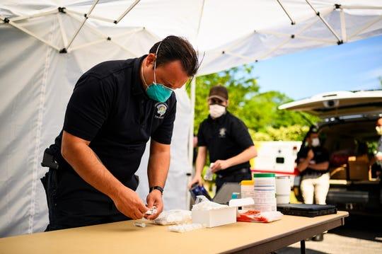 A paramedic prepares coronavirus testing kits at a Prisma Health community testing site at Augusta Heights Baptist Church Saturday, May 2, 2020.