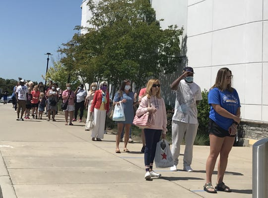 Customers wait in line Saturday morning to enter the Belk store at Haywood Mall in Greenville.