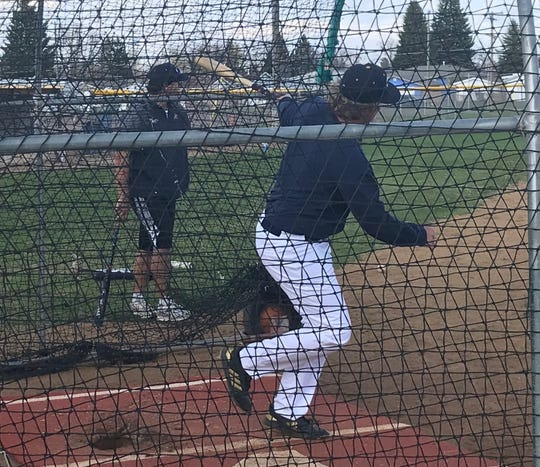 With Great Falls Chargers' pitching coach Tanner Watson (left) looking on, Kael Richards gets some good wood on the ball during the Chargers' batting practice at Don Olson Field.