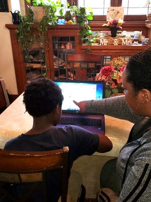 Crystal Manuel of Milwaukee helps her son with a virtual school assignment on Friday, May 1, 2020. Like many parents, she's voiced frustration over Milwaukee Public Schools slower than expected transition to online learning.