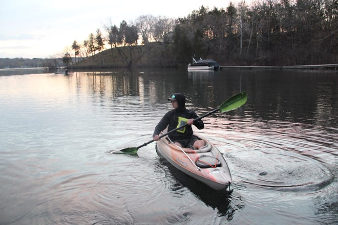 Mick Lewski of Oak Creek paddles his kayak away from the public access on Beaver Lake in Hartland as he prepares to catch up to Isaiah Wolk of St. Francis (left background) on opening day of the Wisconsin fishing season.