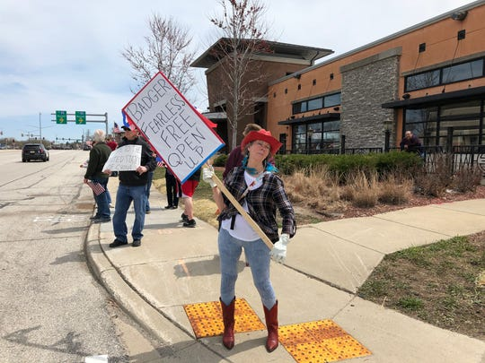 A woman holds up a sign at a protest of Gov. Tony Evers' stay-at-home order near Brookfield Square mall in Brookfield on Saturday.