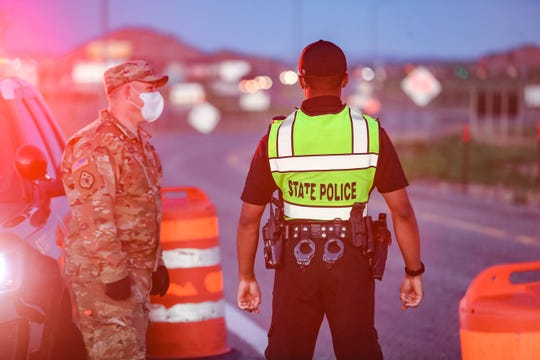 A New Mexico State Police officer and a member of the U.S. Army National Guard stand on the off-ramp of Interstate 40 entering Gallup on Friday, May 1, 2020. The city is closed to all but  residents and essential employees after New Mexico Gov. Michelle Lujan Grisham enacted the state's Riot Control Act in a bid to stop the spread of the coronavirus.