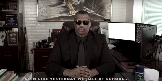 """Pensacola High principal David Williams at his desk during the school's """"We'll Be Missing You!"""" music video honoring students and Class of 2020 seniors during the  COVID-19 pandemic."""