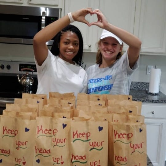 Raegan Jones (left) and Gracie Coleman are excited to bring their Pack-A-Sack donations to the homeless.