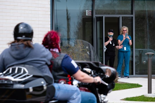Two McLaren Port Huron employees watch from a doorway as a group of more than 200 motorcycle riders pass through the parking lot Saturay, May 2, 2020, in Port Huron. The ride is one of several recent events aimed at supporting frontline workers in the coronavirus pandemic.