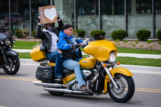A motorcycle rider holds up a painted heart as they ride past McLaren Port Huron Saturday, May 2, 2020, during a parade of more than 200 riders to support frontline workers during the coronavirus pandemic.