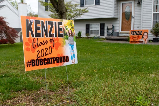 Posters celebrating Makenzie Boyd's upcoming graduation sit in her front yard.