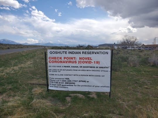 A sign warning people about the COVID-19 virus pandemic near the boundary of the Confederated Tribes of the Goshute Reservation.