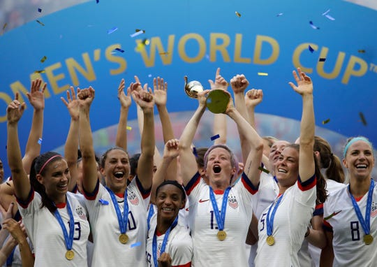 In this July 7, 2019, file photo,  United States' Megan Rapinoe lifts up a trophy after winning the Women's World Cup final soccer match between the U.S. and The Netherlands at the Stade de Lyon in Decines, outside Lyon, France. A federal judge threw out the unequal pay claim by players on the U.S. women's national soccer team but allowed their allegation of discriminatory travel accommodations and medical support services to go to trial.