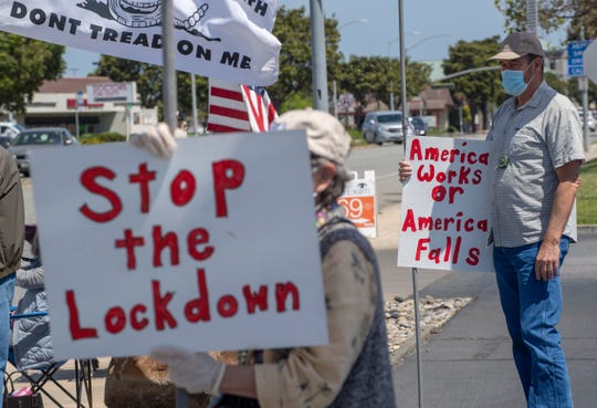 """Harry Allen, 72, born and raised in Monterey County holds a sign that reads """"America works or America Falls"""" during the freedom rally on Friday, May 1, 2020."""