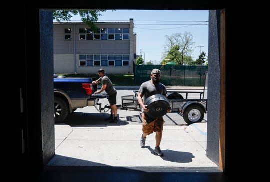 Sammy Ibrahim, an intern at the Royal Barbell Club, carries weights into the gym as the business gets ready to reopen on Monday. The gym has been shut down for about one-and-a-half months due to restrictions put in place to slow the spread of the coronavirus.