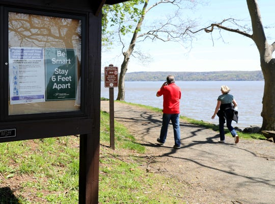 A social distance sign is pictured as walkers take in the view of the Hudson River from Nyack Beach State Park in Upper Nyack, May 2, 2020.