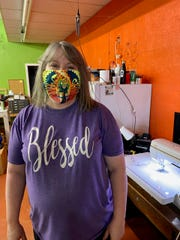 Monica Combs shows off one of the masks she has made for Hotter'N Hell Hundred to sell in their online store. The masks are available in three colors, made from unused 2019 HHH ride shirts.