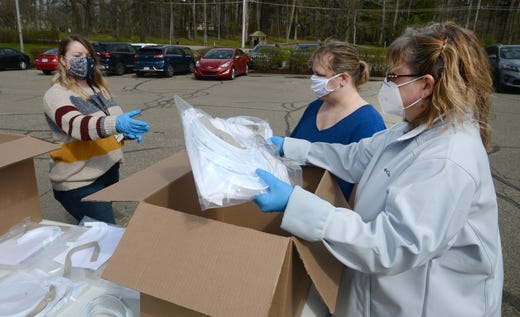 Shelbi Daniels, left, Dawn Hamilton, center, and Heather Kahle, right, of Bliley Technologies hand out face shields free to the public May 2, 2020 at the Millcreek Township business. Bliley Technologies has been assembling and distributing the COVID-19 face shields that were designed at Penn State Behrend and paid for  by the Erie County Gaming Revenue Authority.