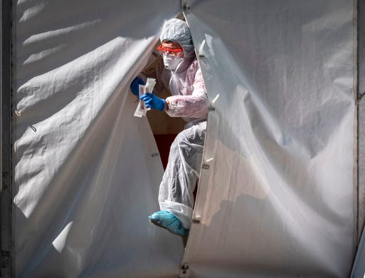 A medical staff gets out from a tent of a testing point for the COVID-19 coronavirus in central Moscow on May 2, 2020.