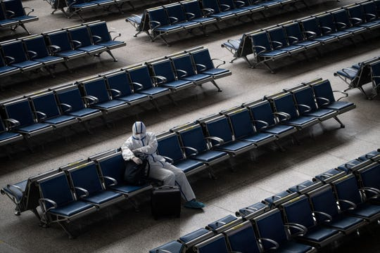 A passenger wears a hazmat suit as a precaution against the COVID-19 coronavirus as he waits for a train at Hankou Railway Station in Wuhan, in China's central Hubei province on May 2, 2020.