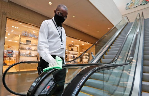 Amid concerns of the spread of COVID-19, Curtis Sulcer wipes down an escalator for shoppers at the North Park Mall in Dallas, Saturday, May 2, 2020. Texas charged into its first weekend of re-opening the economy with residents allowed to go back to malls, restaurants, movie theaters and retail stores in limited numbers.