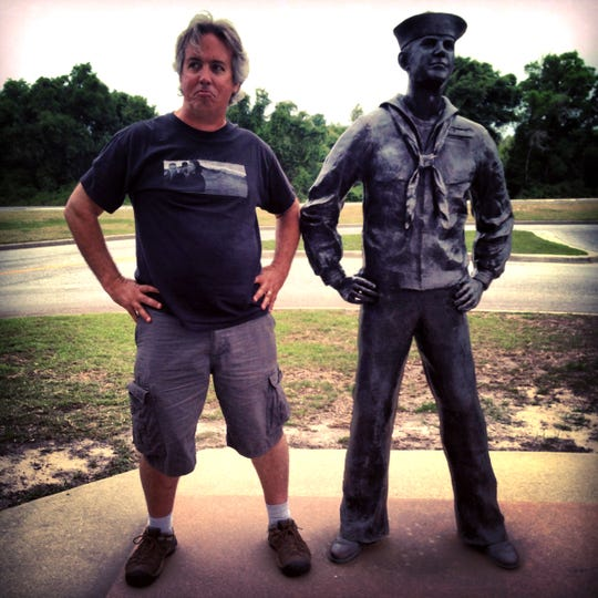 Ron Erdrich outside beside a sailor statue at the National Naval Aviation Museum at NAS Pensacola May 1, 2013. Erdrich trained on that base in 1985 at the U.S. Naval Schools of Photography.