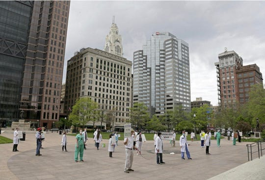 Doctors and other medical workers wearing masks and staying six feet apart demonstrate outside the Ohio Statehouse on Sunday in support of actions taken by Dr. Amy Acton of the Ohio Department of Health to counter the coronavirus pandemic. The Physicians Action Network organized the event.