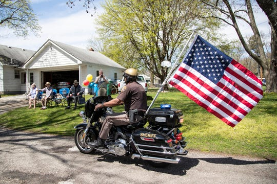 Oakland County deputy sheriff Sean Galloway brings a flag as gift to Jim Curry, a World War II veteran, who is turning 100 on Monday, outside of Curry's home in Commerce Township, Sunday, May 3, 2020.