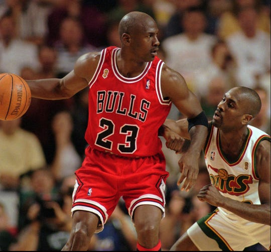Chicago Bulls' Michael Jordan looks to move around the Seattle SuperSonics' Gary Payton during the third quarter of Game 3 in the NBA Finals, Sunday, June 9, 1996, in Seattle.